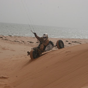 Kite Buggy navigating down a sand dune with the ocean in the background